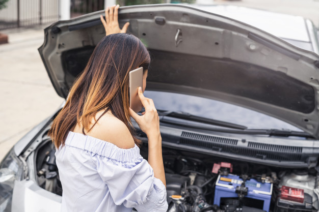 young-woman-with-broken-down-car-using-smartphone-for-assistance_44943-400